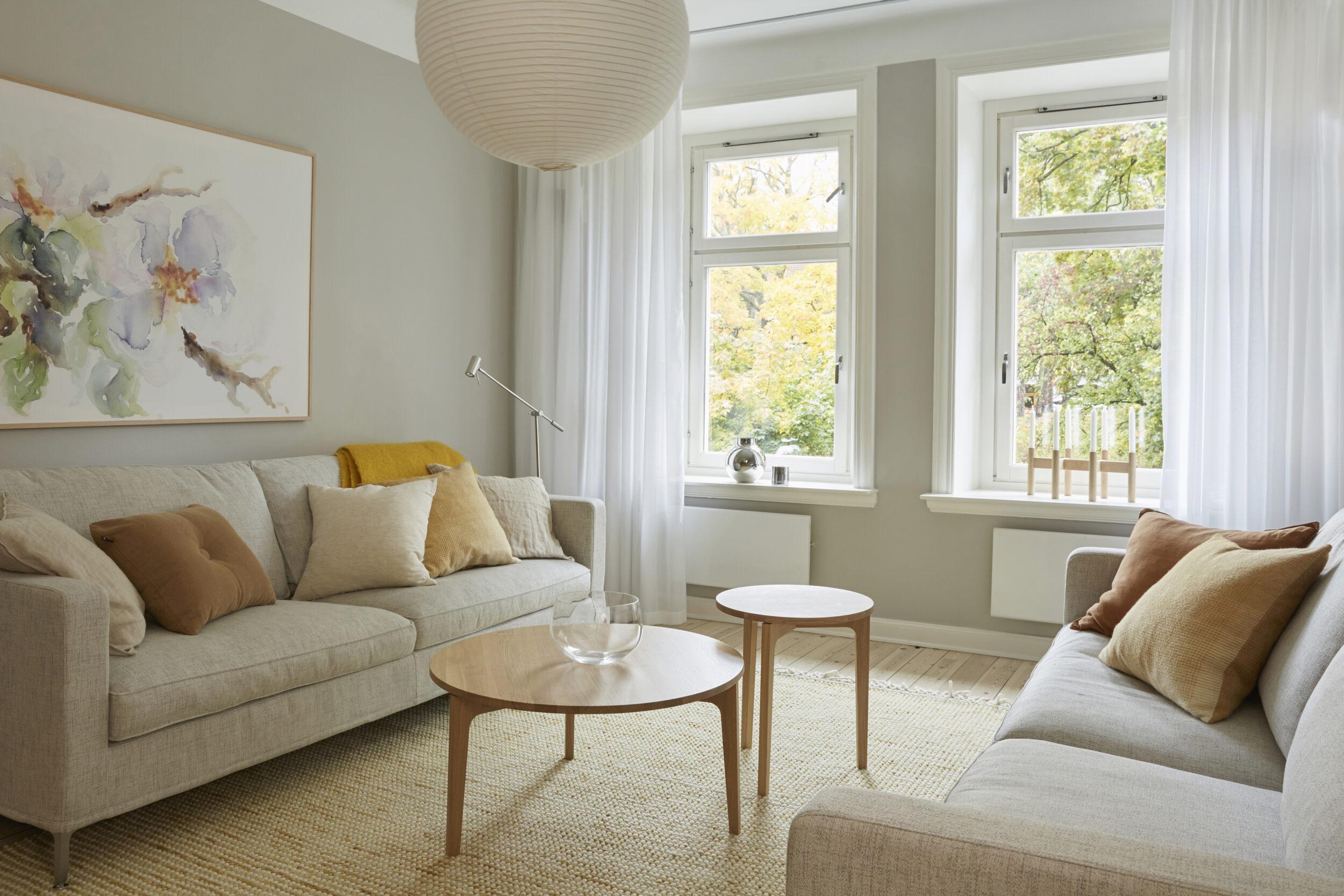 Vardagsrum med gardiner och gul matta, två soffor mittemot varandra