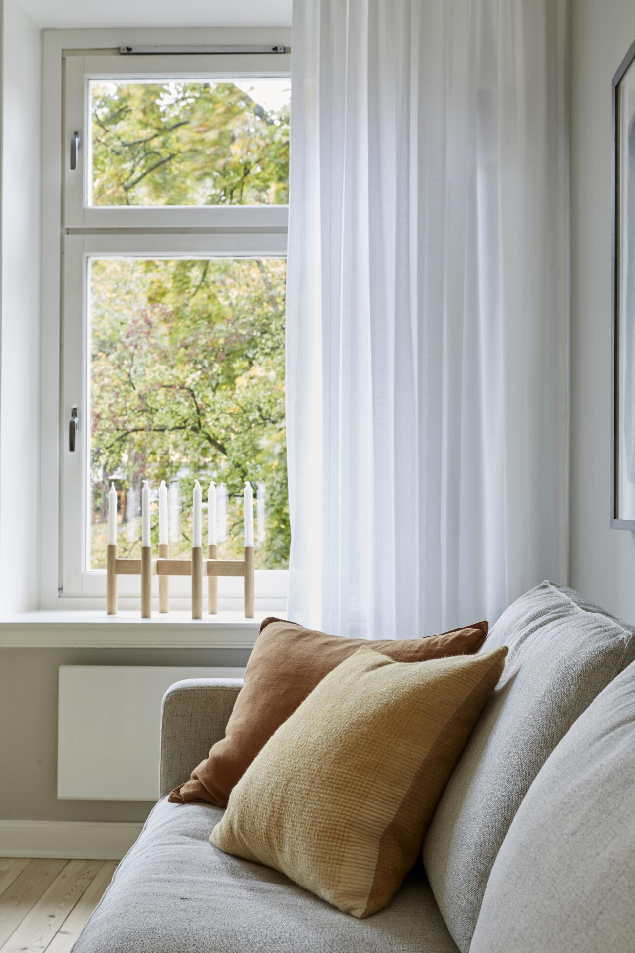 Grå soffa vid ett fönster, och en ljusstake i ek